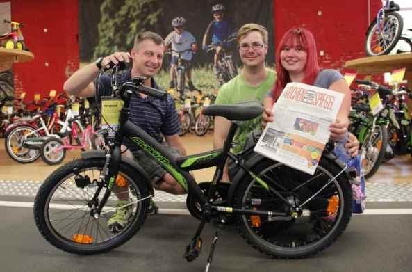 """Lucky Bike-Filialleiter Nils Stannewitz (l.) übergibt das 20 Zoll Bike """"Sevilla Basic Banana"""" an die Deans Eltern Norman und Jenny. Foto: bit"""