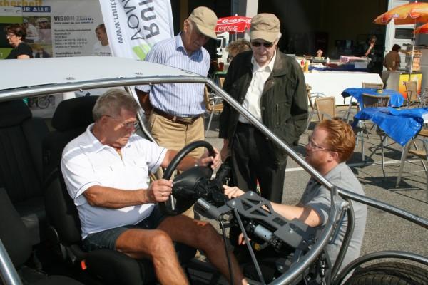 Patrick Staack (Hocke) vom Deutschen Verkehrssicherheitsrat (DVR) erklärt interessierten Besuchern die ideale Sitzposition im Fahrzeug- und wie sich diese im Falle eines Unfalls auf die Reaktionsmöglichkeiten des Piloten auswirken kann.        Foto: C. Haase