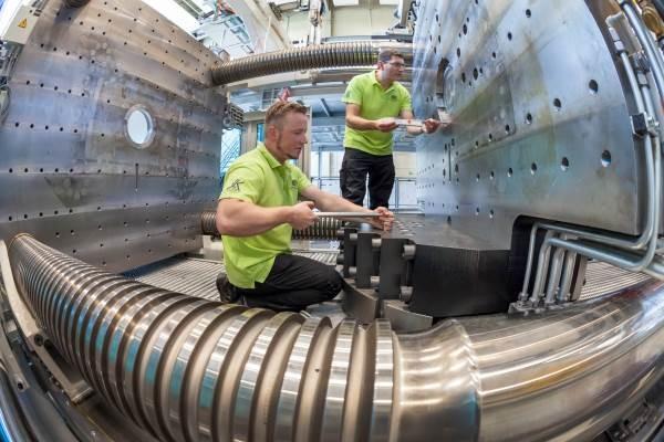"""Enge und intensive Verzahnung zwischen Forschung und Industrie wird für den sächsischen Maschienbau immer wichtiger. Mit der Fertigstellung des 1. Bauabschnittes der Forschungshallen für den Bundesexzellenzcluster """"Technologiefusion für multifunktionale Leichtbaustrukturen"""" (MERGE) erhielt die Technische Universität Chemnitz einen ganz außergewöhnlichen """"High-Tech-Baustein"""" für Forschung und Lehre. Das Herzstück der neuen Forschungseinrichtung ist die sogenannte MERGE-Maschine, die zur kombinierten Verarbeitung von kunststoff- und metallbasierten Werkstoffen mit Hilfe der Basistechnologien Umformen und Spritzgießen genutzt wird. Foto: Uwe Meinhold"""