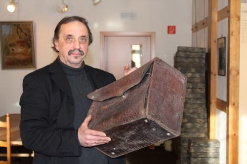 Restaurator Thomas Heinicke aus Wickersdorf mit einem historischen Reisekoffer des Lichtensteiner Museums. Er hat auch schon wertvolle Taschenuhren zum Schätzen vorgelegt bekommen. Foto: Uwe Wolf