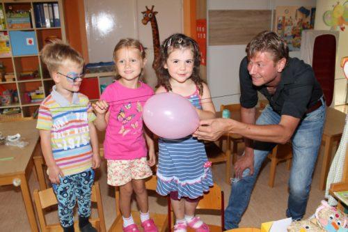 Jake, Leoni und Tina von der Schmetterlingsgruppe sind begeistert, wie Michael Gobsch mit einem Luftballon ein kleines Röhrchen am Faden gleiten lassen kann. Foto: Uwe Wolf