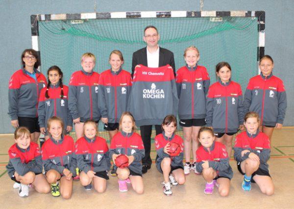 Die Trainerin (h.l.) und die Mädchen der E-Jugend des Handballverein Chemnitz freuen sich riesig über die gesponserten Jacken von Rajko Müller, dem Inhaber von Omega Küchen (h.m.). Foto: Nicole Neubert