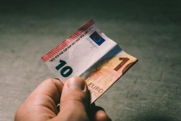 Mann hält einen Euroschein in der Hand.