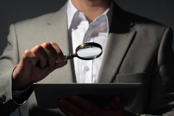 Ein Mann nimmt eine Webseite unter die Lupe